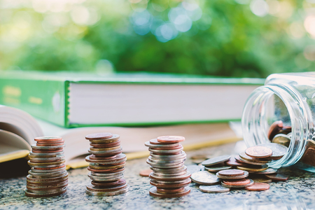 Pile of money coins in the glass jar with books on blurred natural green background and added colour filter for financial and education concept Stock Photo