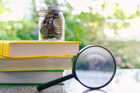 Geldmünzen im Glasgefäß auf den Büchern und der Lupe auf unscharfem natürlichem grünem Hintergrund für Finanz- und Bildungskonzept Standard-Bild