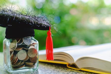 コインのガラス瓶と正方形のアカデミックキャップと教育、金融と貯蓄お金の概念のためのぼやけた自然な緑の背景に本を開きました