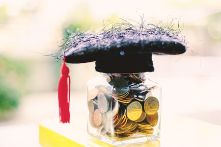 Square academic cap with the glass jar of coin on the book against blurred natural green background for education, finance and saving money concept