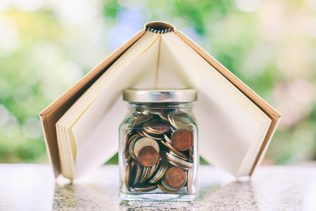 Blank notebook roof cover the glass jar of coins against blurred natural green background for planning investment, business, finance and property concept