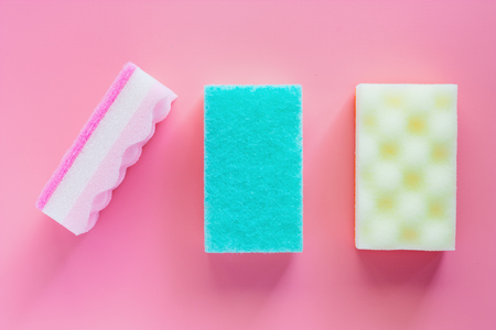 Scrub sponge on pink background for kitchen cleaning. Flat lay and top view image.