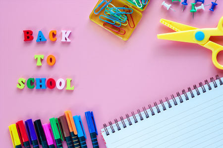 School supplies with notebook, coloured pen, scissors, binder clip, push pins and wooden text BACK TO SCHOOL on pink background for education concept Archivio Fotografico - 106663762