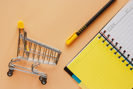Mini shopping cart or trolley with opened spiral notebook and pen on beige color background for spending plan concept