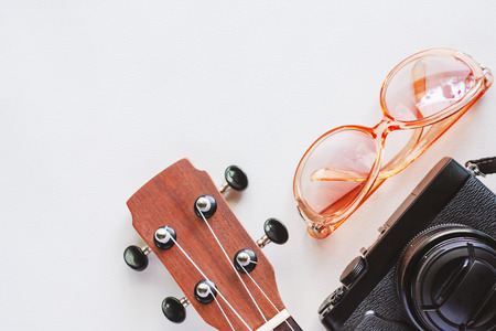 Ukulele with sunglasses and camera on white background for travel accessories and relaxation concept