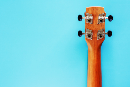 Back of ukulele neck on blue background for musical instrument, hobbies and relaxation concept