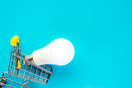 Glowing LED light bulb with mini shopping cart or trolley on blue background for energy savings concept
