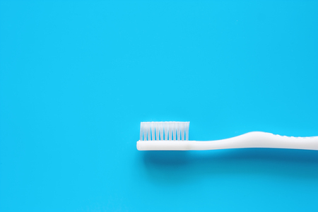 White toothbrush used for cleaning the teeth on blue background for dental care concept