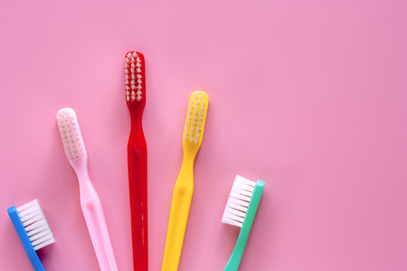 Toothbrush used for cleaning the teeth on pink background for dental care concept