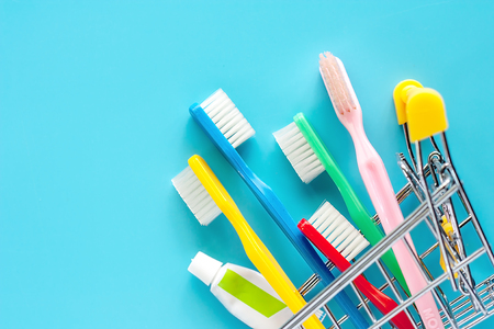 Shopping cart with toothbrush and toothpaste on blue background for market and dental care concept