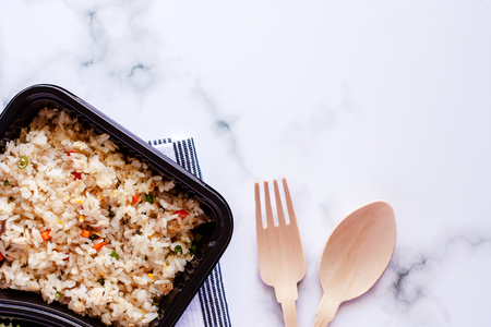 Delicious fried rice in lunch box with napery, wooden spoon and fork on marble background for ready to eat and food concept Standard-Bild