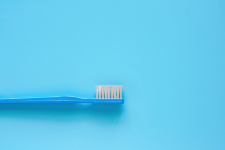Toothbrush used for cleaning the teeth on blue background for dental care concept