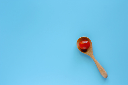 Fresh red tomato in wooden spoon on blue background for diet and heathy eating concept