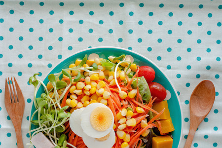 Fresh salad vegetable with boiled chicken egg, wooden spoon and fork on blue polka dot fabric or tablecloth background for healthy eating and diet food concept