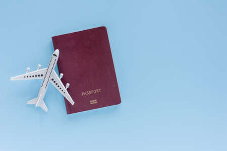 White airplane model with passport on blue background for travel and journey concept
