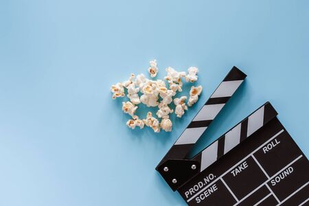 Movie clapper board with popcorn on blue background for entertainment concept