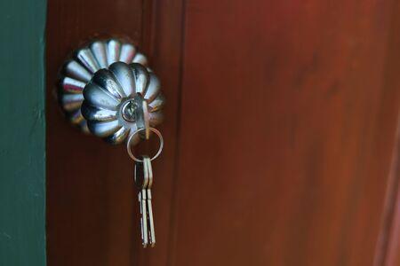Close up of door knob with key  on wooden door for unlock to enter the room. 版權商用圖片