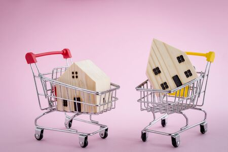 Wooden house model in the shopping cart on pink background for housing and property concept