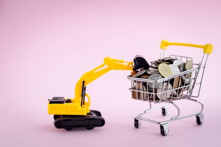 The excavator loader model with pile of coins in the shopping cart on pink background for saving money, investment, business and finance concept