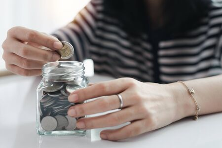 Woman's hand saving a coin for planning, housing and property financial concept