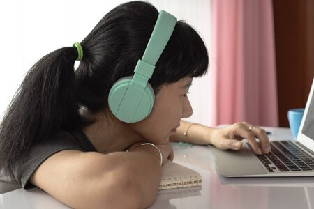 Woman wearing headphones, using laptop and staying at home for self-quarantine, staying home and social distancing in coronavirus or Covid-2019 outbreak situation