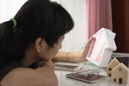 Woman looking at the clock, feeling lonely, want to go home and miss home with Thai passport and the plane and house model in coronavirus or Covid-2019 outbreak situation Imagens