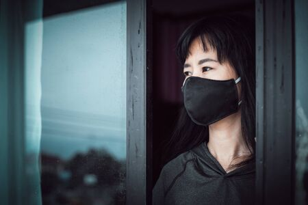 Asian woman wearing a black face mask, standing absent-minded at the door and staying home for self-quarantine and social distancing in coronavirus or Covid-2019 outbreak situation concept Imagens