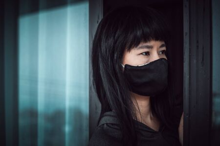 Asian woman wearing a black face mask, standing absent-minded at the door and staying home for self-quarantine and social distancing in coronavirus or Covid-2019 outbreak situation concept 写真素材