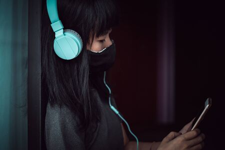 Asian woman wearing a black face mask and headphones, using smartphone and staying home for self-quarantine and social distancing in coronavirus or Covid-2019 outbreak situation concept