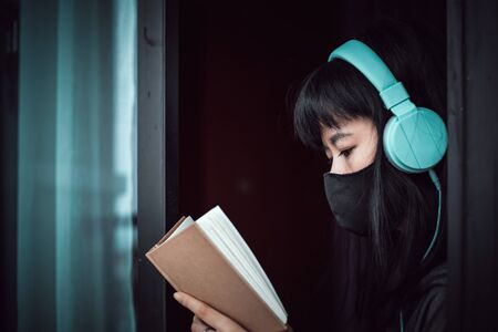 Asian woman wearing a black face mask and headphones, reading a book and staying home for self-quarantine and social distancing in coronavirus or Covid-2019 outbreak situation concept