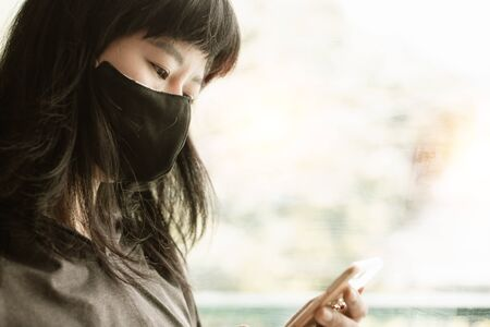 Asian woman wearing a black face mask, using smartphone at the door and staying home for self-quarantine and social distancing in coronavirus or Covid-2019 outbreak situation concept