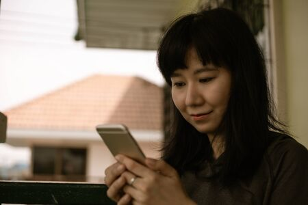 Asian woman using smartphone and staying home for self-quarantine and social distancing in coronavirus or Covid-2019 outbreak situation concept