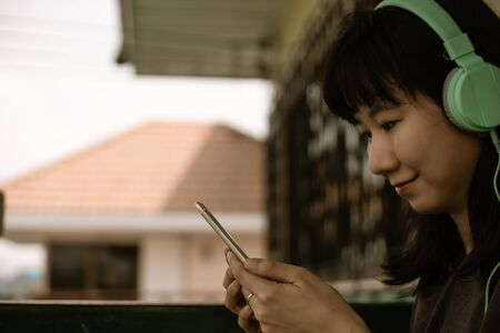Asian woman wearing headphones, using smartphone and staying home for self-quarantine and social distancing in coronavirus or Covid-2019 outbreak situation concept