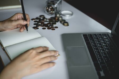 Woman's hand writing a note for planning and saving money with coins in the glass jar and computer laptop for business and finance concept Imagens