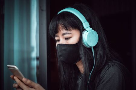 Asian woman wearing a black face mask and headphones, using smartphone and staying home for self-quarantine Imagens