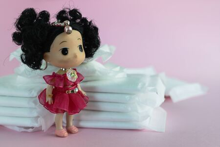 Feminine sanitary napkin, an absorbent item worn by a woman while menstruating, with blurred lady doll on pink background for hygiene and health concept Imagens