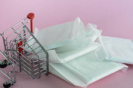 Feminine sanitary napkin, an absorbent item worn by a woman while menstruating, with shopping cart on pink background for hygiene and health concept