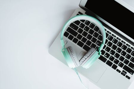Top view of headphones with computer laptop on white office desk for entertainment and leisure online concept