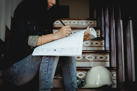 Asian woman looking architectural plan, sitting on the stairs and working at home