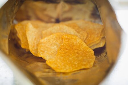 Close up of baked potato chips in opened snack bag for food concept