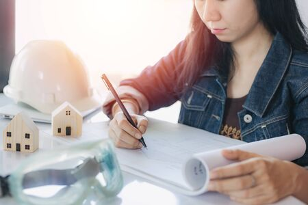 Asian woman checking architectural plan with personal safety equipment and wooden house model on white office desk for building inspection concept