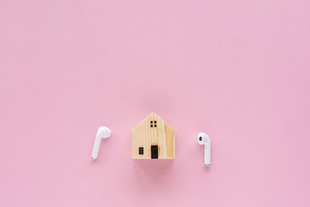 Wooden house model with wireless headphones on pink
