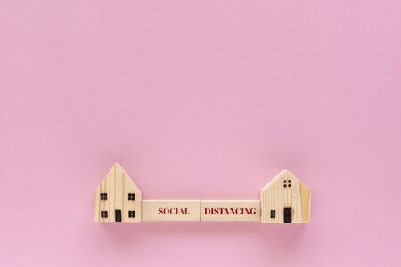 Wooden house model with social distancing text on pink