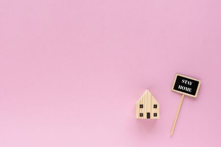 Wooden house model with stay home text on pink Imagens