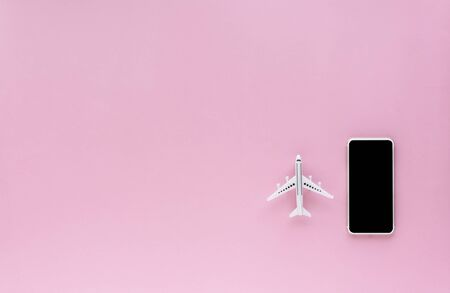Blank screen of smartphone with white airplane model on pink