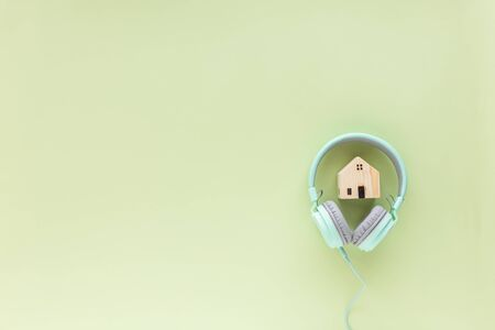 Green headphones with wooden house model on green