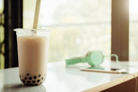 Bubble tea in plastic cup on white table with blurred background for drinks and beverage at home concept
