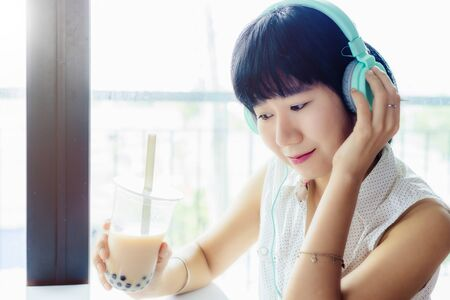 Asian woman wearing headphones and holding a plastic cup of bubble tea Imagens