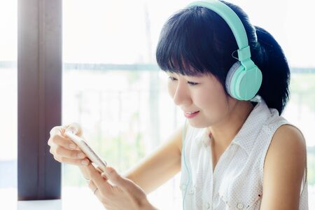 Asian smiling woman wearing headphones, listening music and using smartphone