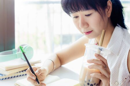 Asian woman working and drinking bubble tea